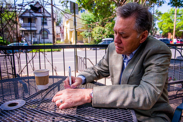 Man writing at an outdoor tble.