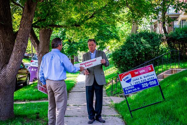 Andrew Nagel and John Sullivan put up a Neighborhood Expert sign.