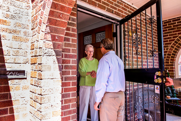 Man greets older woman at her front door.