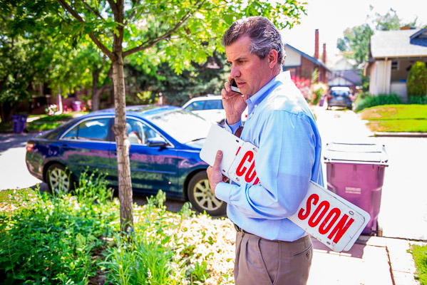 Day in the life of a realtor man on the street talking on his phone carring a real estate sign.