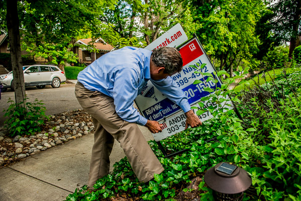 Andrew Nagel hangs his name on his real estate sign.