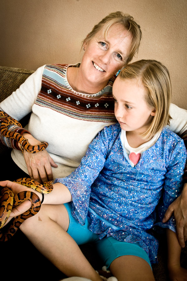 Woman and girl posing together with snakes.