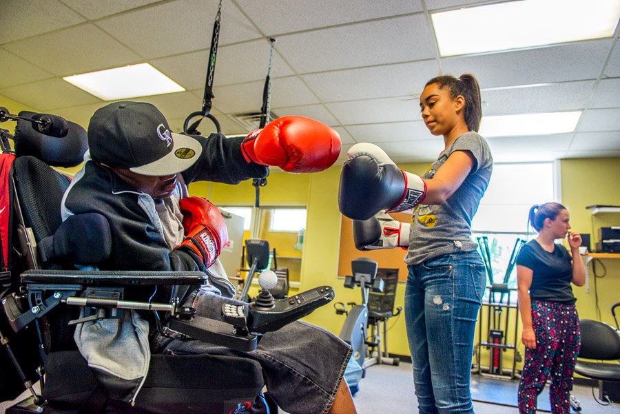 Man with MS in a wheelchair wearing boxing gloves takes a swing.