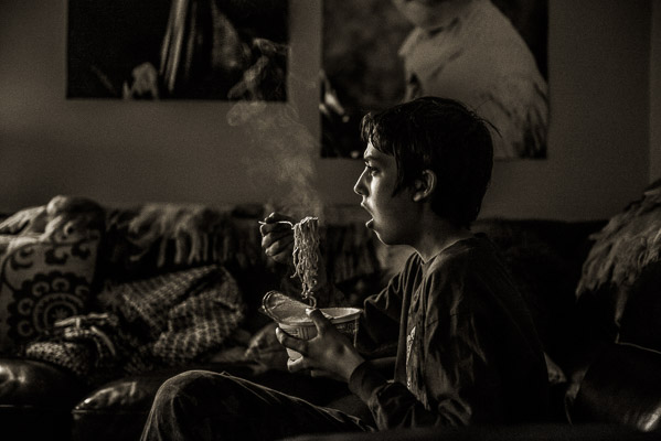 Boy eating steaming noodles.