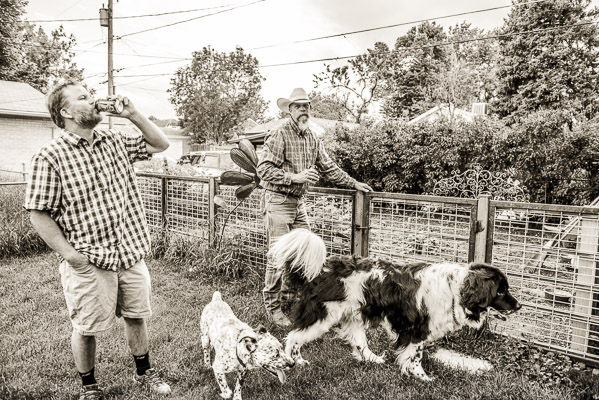 Men drinking beer, hanging out with dogs.