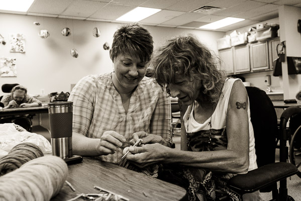 An aide helps a woman with her crochet project.