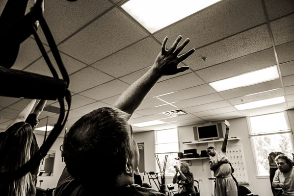 Black and white of a man stretching in exercise class.