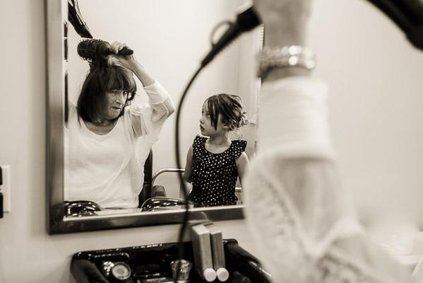 Grandma blowdries her hair while grandaughter watches in mirror