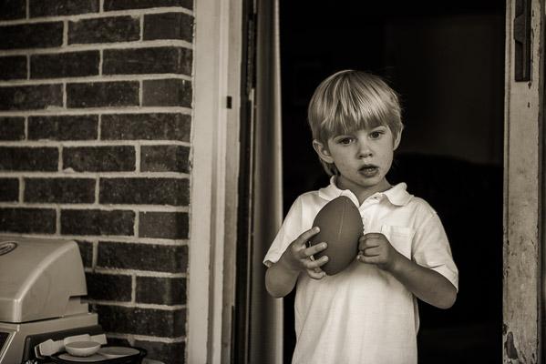 Little boy holds a football in a doorway.