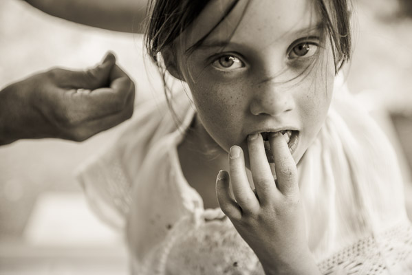 Little girl wiggles a loose tooth.