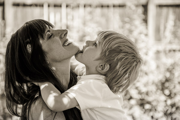 Little boy licking his mom's chin.