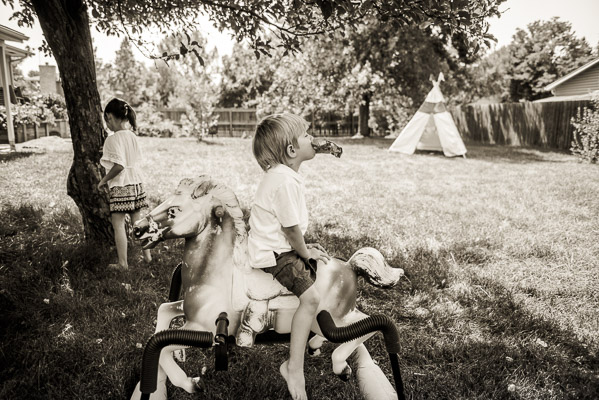 Kids playing in the yard with a plastic horse on springs and a teepee in the background.