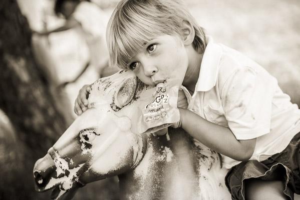 Closeup of little boy on plastic horse drinking a juice box.