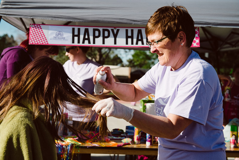 one of the volunteers spraying color into a girl's hair