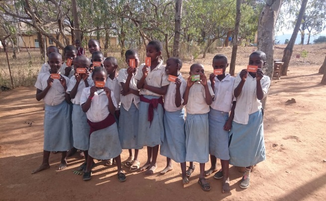 Girl pupils hold up their iMlango cards at Kalamba primary school