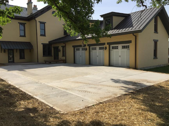 Expanded driveway pad behind farmhouse and seeded lawn