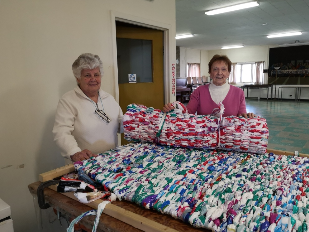 Two Summerlea volunteers with a milk bag mattress.