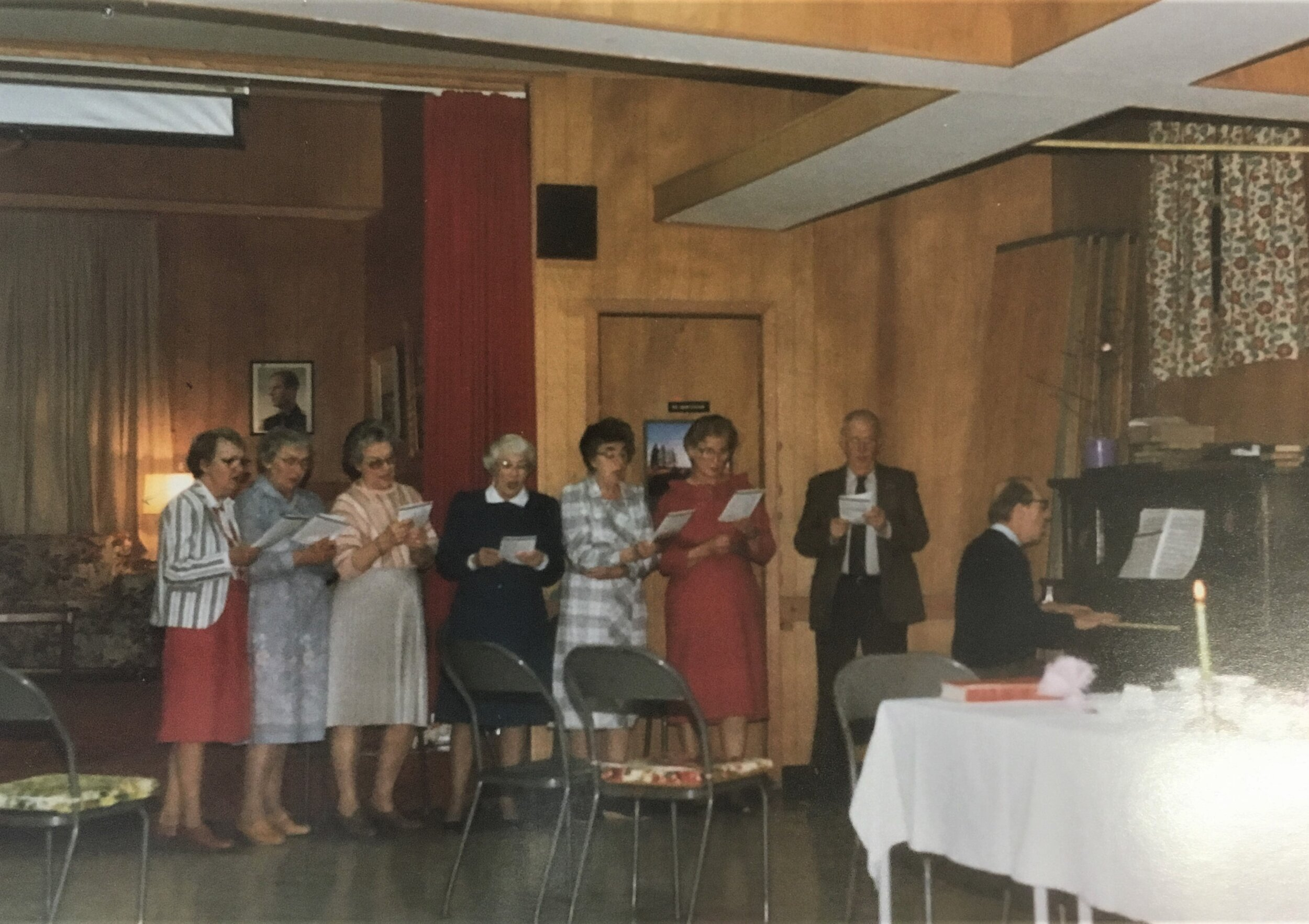 4. A Choir Party in the Crawford Park hall in 1985. Pictured, left to right: Jean Abbott, Mary McDowall, Hazel Long, Jean Gillebrand, Marg Bowker, Louise Smith, Cliff Gillebrand and Bill Bowker at the piano. Note that the stage, currently in use as our office, was set up as a sort of lounge, with photos of Queen Elizabeth and Prince Philip on the walls.