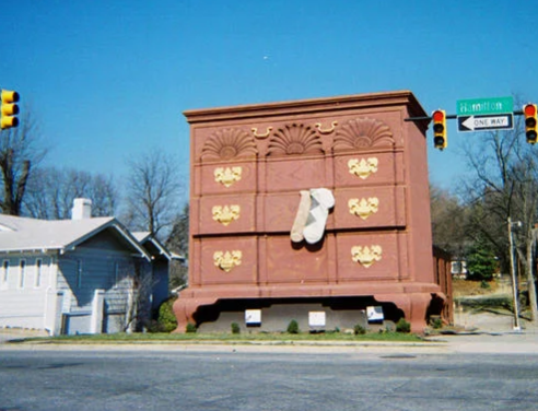 """The World's Largest Chest of Drawers, High Point, NC High Point bills itself the """"Home Furnishings Capital of the World,"""" so a 32-foot-tall, freestanding chest of drawers, complete with 6-foot-tall socks, in the middle of town makes perfect sense. It's for sale -- insert dirty lingerie jokes here.  https://www.topixoffbeat.com/slideshow/19342 Stacie Hougland"""