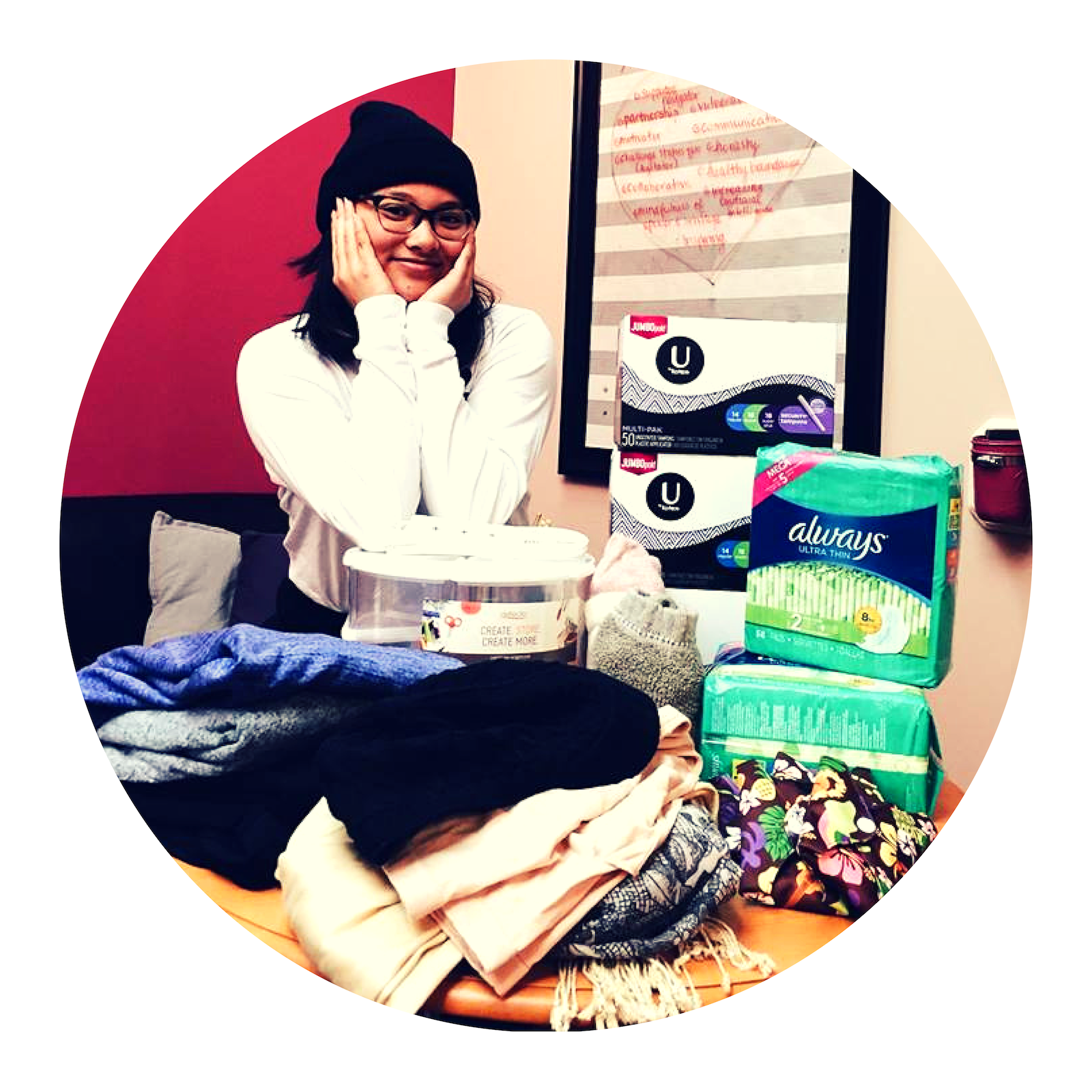 A staff member smiling above a recent box of donations of menstruation pads, tampons, clothing, and more!
