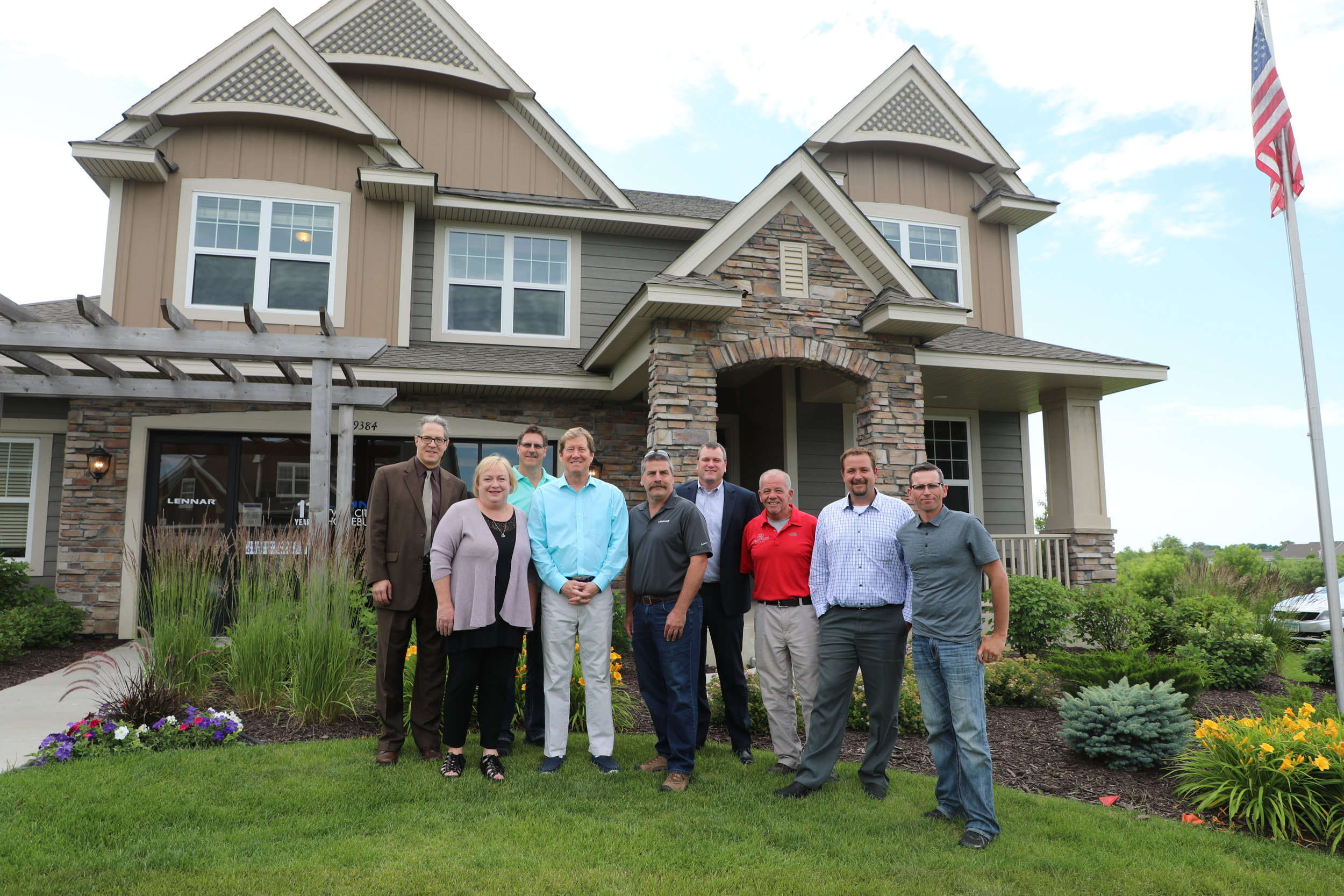 Housing First Minnesota members pose for a picture with Congressman Jason Lewis (CD2-R) outside a Lennar Minnesota model home in Lakeville, MN.