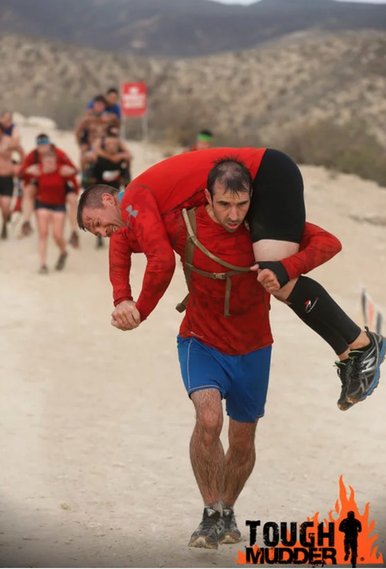 Chief Petty Officer Craig 'Morbs' Morby-Jones, Royal Navy, gives a lift to Major Greg 'Metro' Stack, United States Air Force, during the Warrior Carry obstacle.