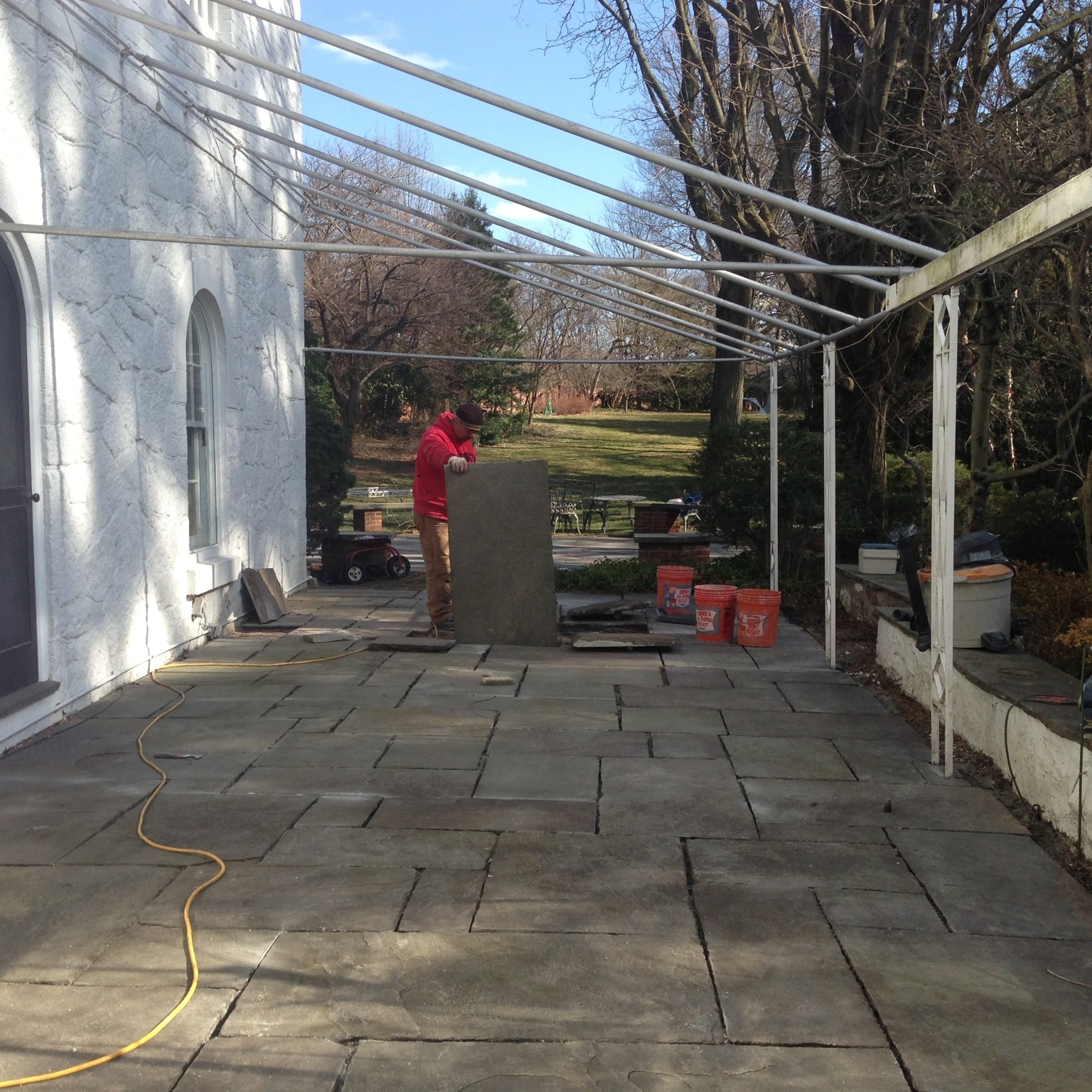 Project site photo of one of our masons fitting the last thick slab of aged flagstone into place. Notice the cleanliness of the work site. We would later repoint all the joints with dry lime mortar and special polymeric paver sand.