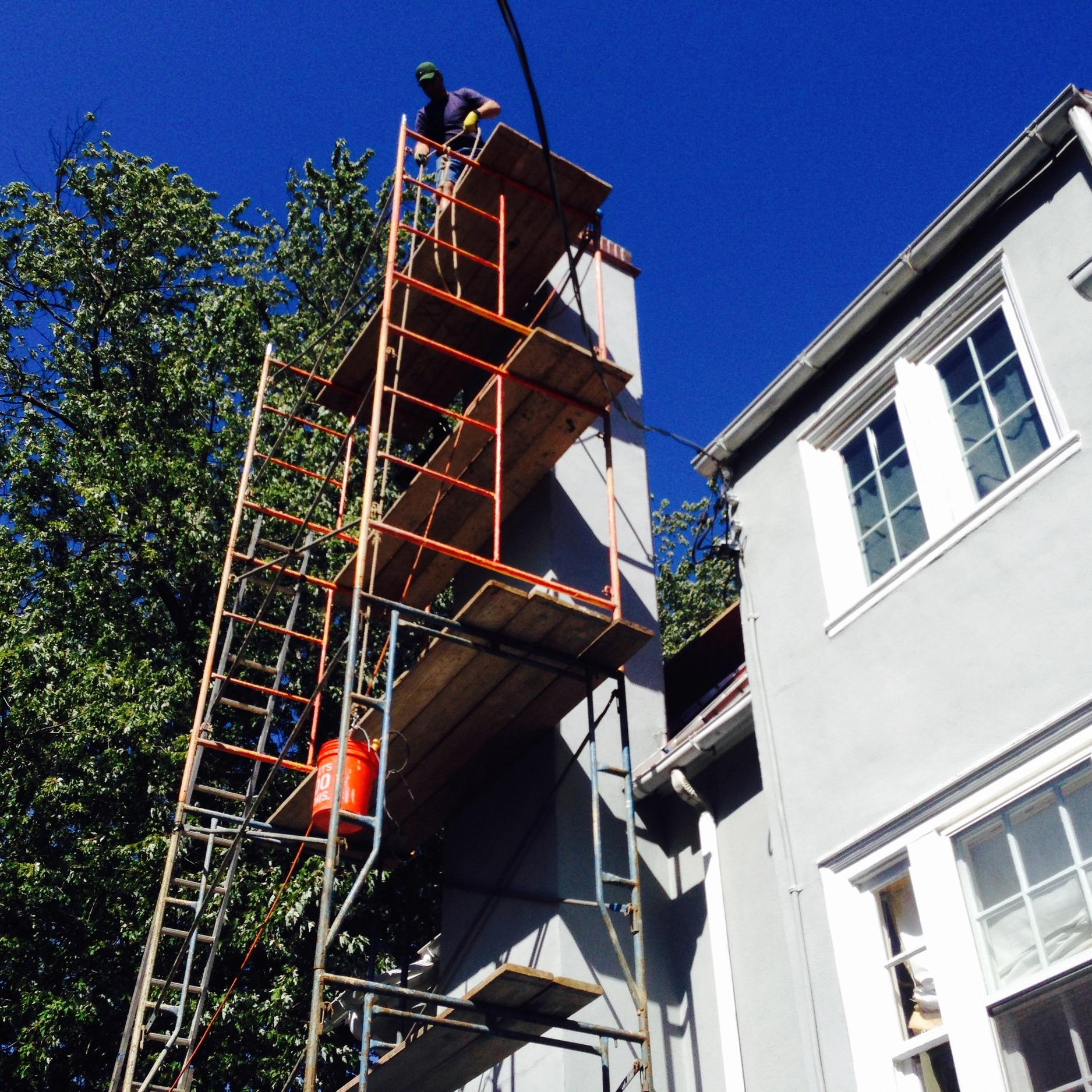 Don't ever let a mason work off only a ladder! We can build scaffolds for any chimney size and height. And, in case you are curious about this project, improper flashing and a loose chimney cap allowed moisture to get behind most of the stucco – and supporting wire mesh, which corrodes, unlike fiberglass mesh or traditional wood lath. This is why we hate working on McMansions, which are designed to fall apart…