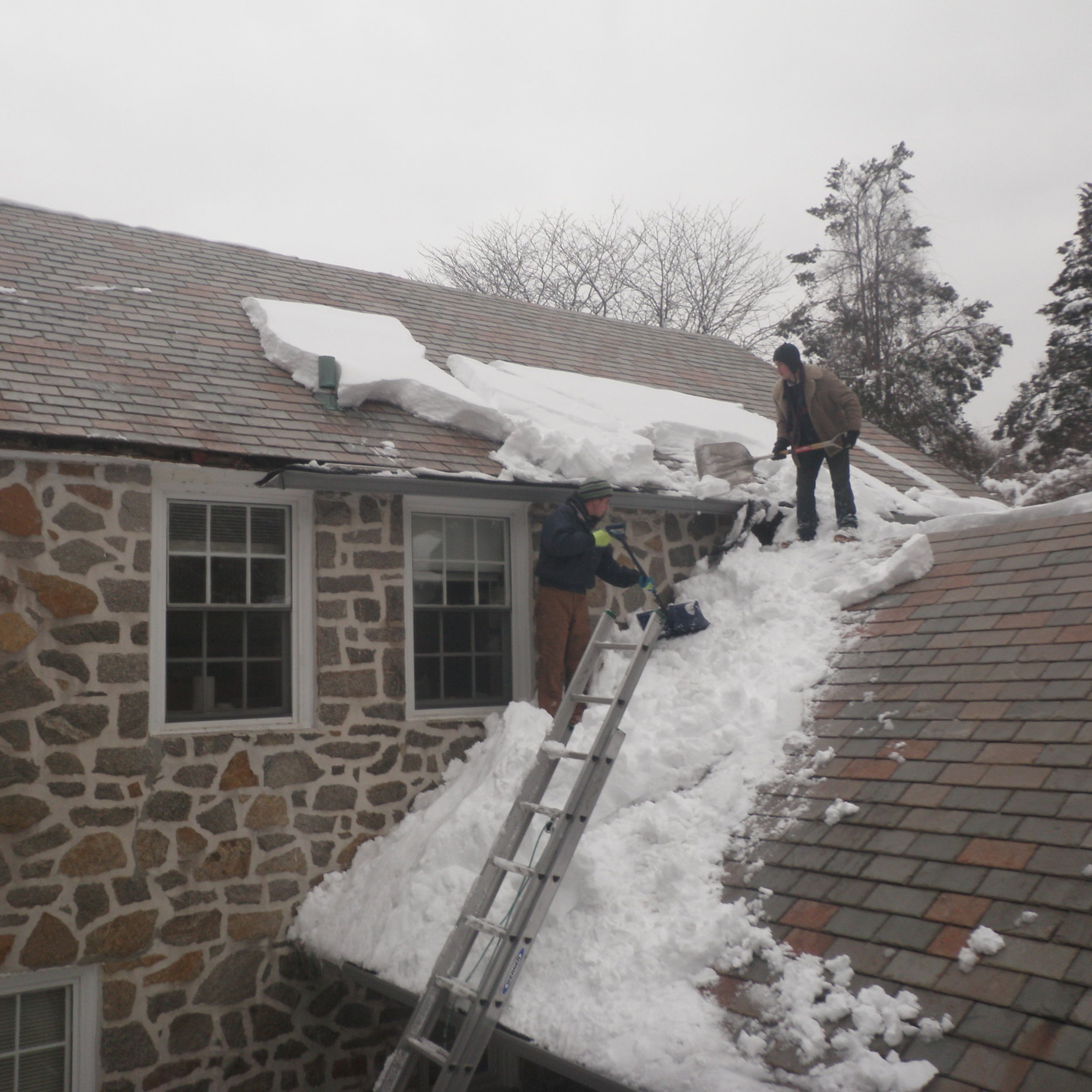 Emergency snow removal service for a customer affected by the historic blizzard of 2010. If snow guards had been installed along the starter courses, such drifts of heavy, wet snow probably would not have amassed, melted, and later refrozen over the once noble and now malformed gutters / fascia –especially on the upper roof, to the left.