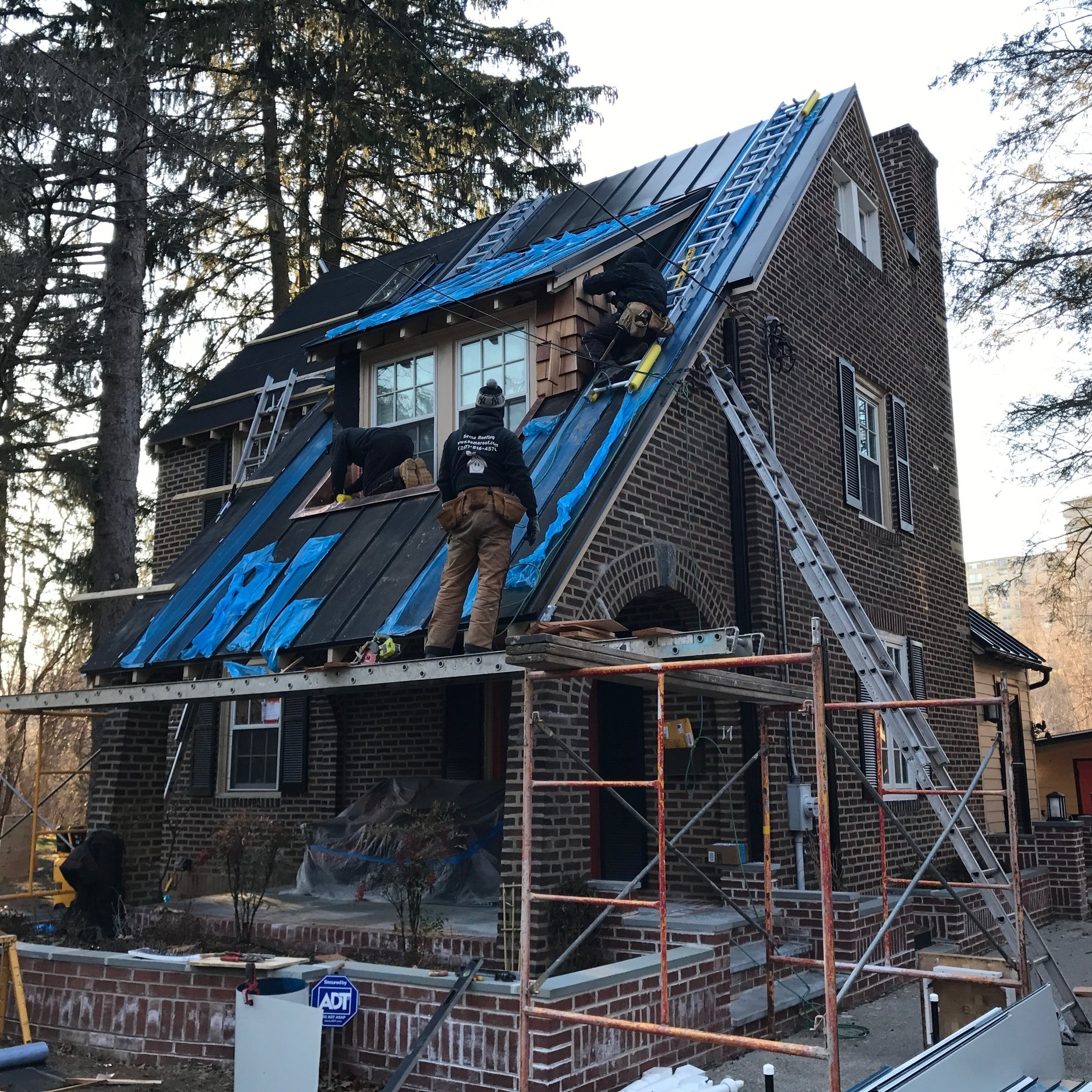 Project site photo of our team installing a steep Vermont-style standing seam metal roof and ice cleats, as well as a cedar-lined dormer and copper flat roof (with sacrificial galvanic buffers), on this early Depression-era pattern book home, in Bryn Mawr.
