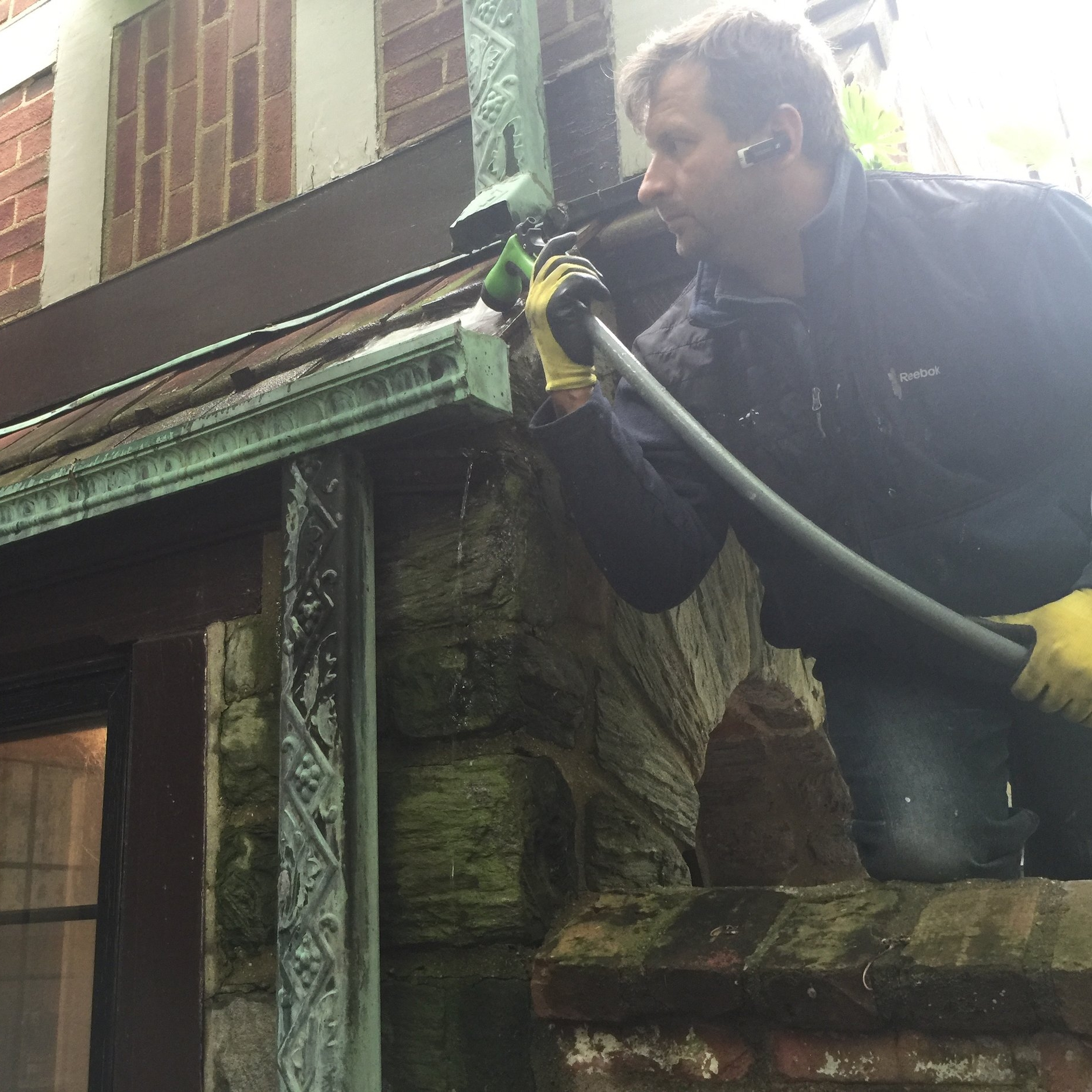Project site photo of our workers testing out an ornamental downspout that we would later rehabilitate. Note: given that the gutter had insidiously leaked for so long that the underlying masonry had weathered away, we would also simultaneously rebuild the adjoining wall and interior woodwork.