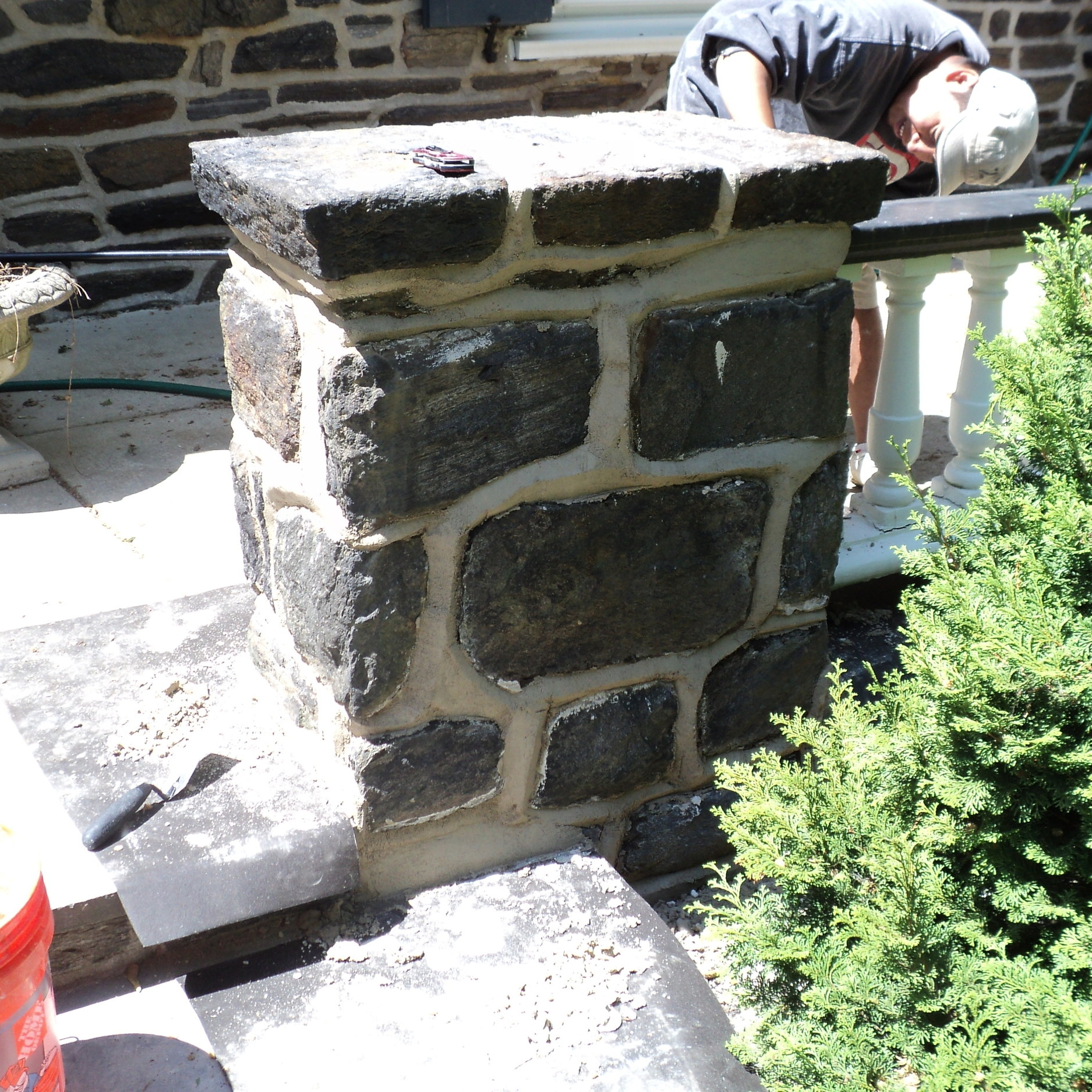 Project site photo of one of our masons applying a lift of natural hydraulic lime mortar –a more flexible and breathable formulation, imported from Dordogne, France, that the National Park Service often specifies for the rehabilitation of historic masonry –to the joints of a traditional pillar. Note: we added black slag fleck and oyster shell inclusions to help mimic the color and texture of the surrounding masonry joints.