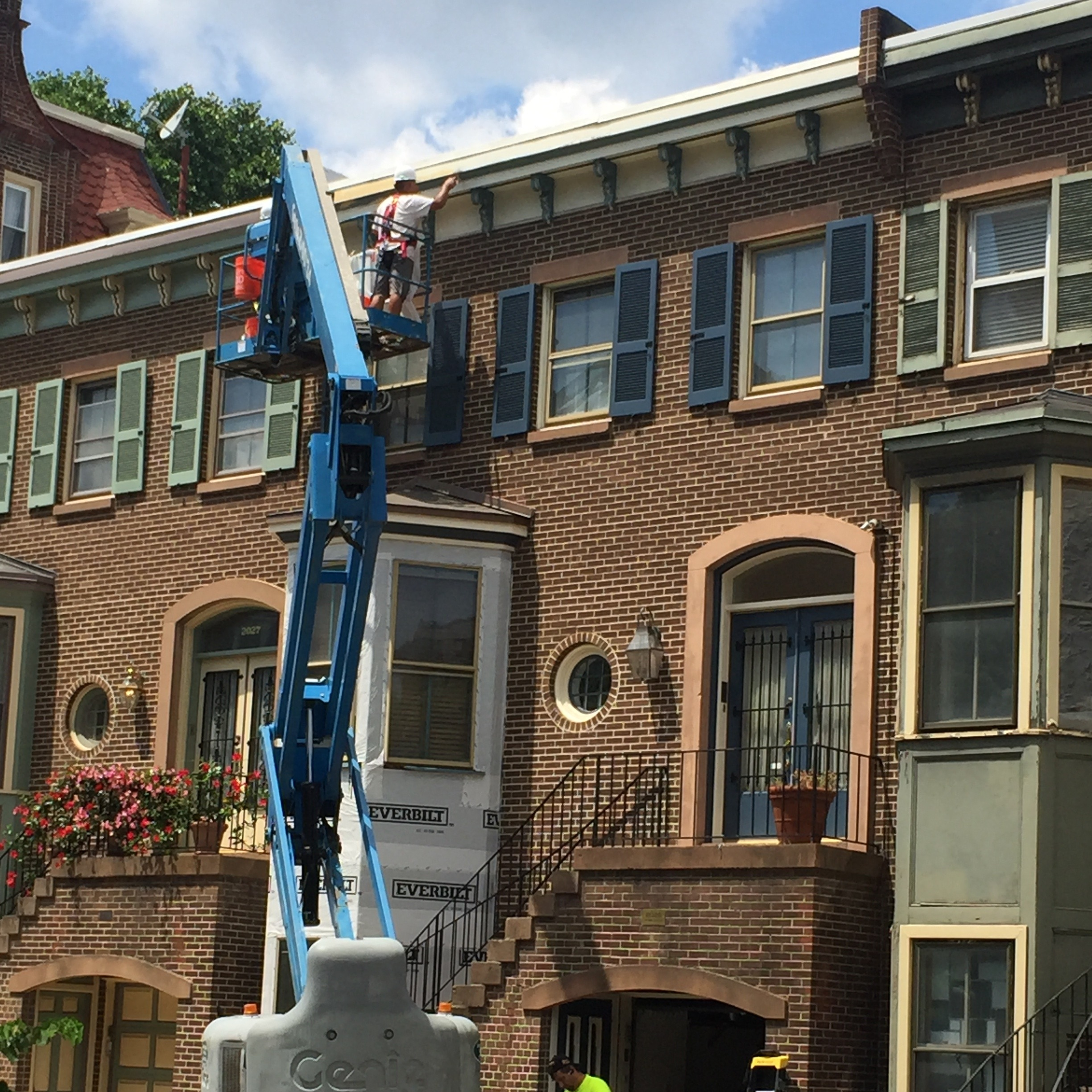 Project site photo of one of our carpenters restoring the fascia, soffit, and ornamental cornice of this Philadelphia townhouse, via high reach.