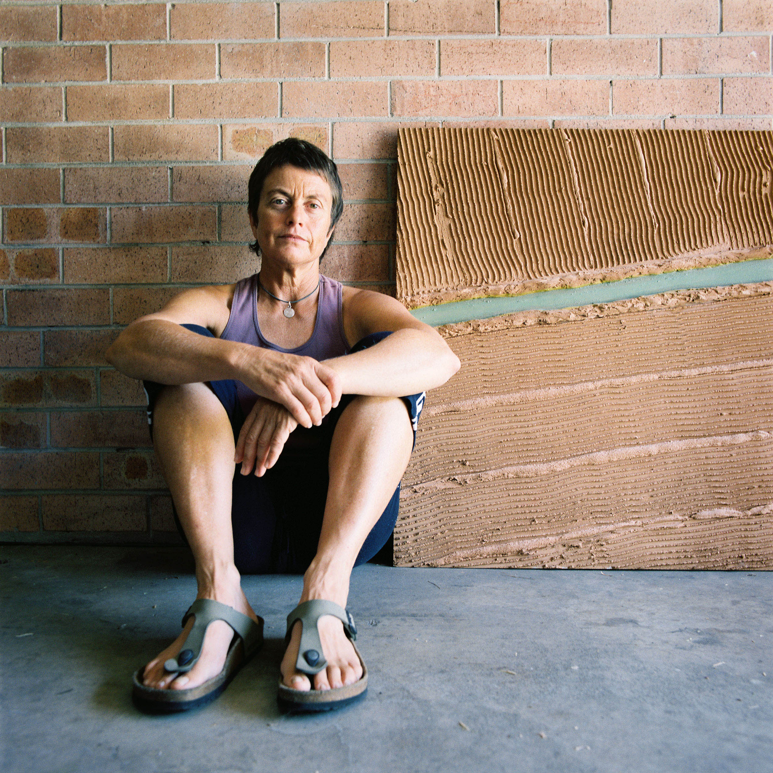 "Artist Kim Williams at her home in Port Kembla, NSW 2010, with a mixed media work titled 'Channel Country #1.' Says Kim, ""the drought has had a big influence on my work in the past couple of years – not just my direct experience of drought and seeing the effect of the drought on rural areas, but also the political ramifications of drought and its prominent place in our national story at present."" - Interview 11.03.2010."