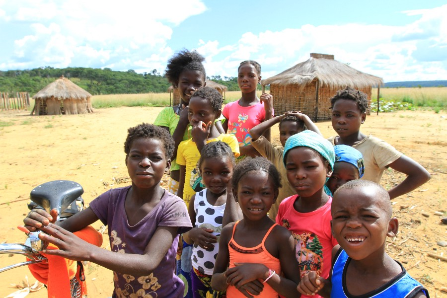 Above: With meat being sold to towns, women and children subsist on cassava cakes, which are not enough to sustain them but are the main crops resilient to the nutrient-deficient soils in the Okavango Wilderness Project study area. Below: Luchaze children. Photos: Chris Boyes