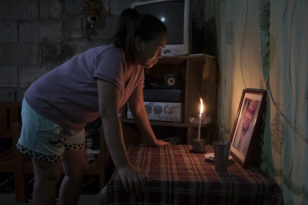 Julie lights a candle at dusk for her son, who was killed by masked policemen last June—one of thousands of who have been killed in Duterte's violent campaign against drugs. Masked policemen entered their home in the middle of the night and killed her son. Photo: Ed Ou