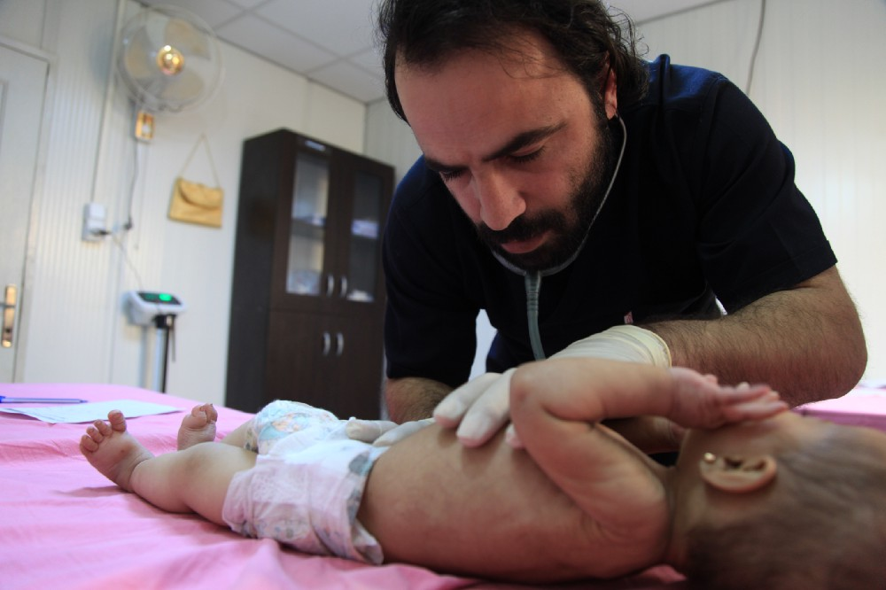 Dr Hatem, the medical director of Hope Hospital, examines a baby for signs of dehydration and malnutrition.