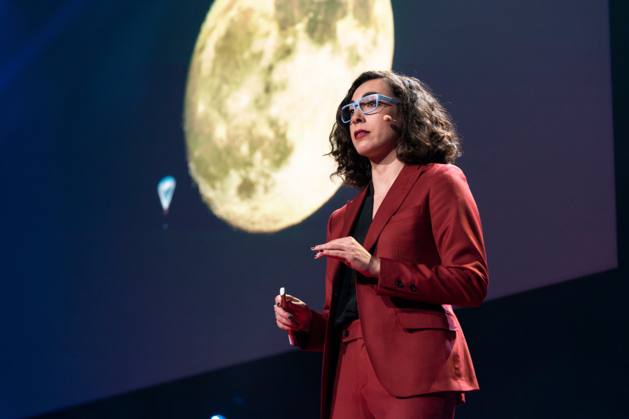 Erika Hamden shows a view of the Moon next to, at lower left, a giant balloon carrying a space telescope she and her team designed. She speaks during TED Fellows Session 2 during TED2019: Bigger Than Us, on April 15, 2019 in Vancouver, BC, Canada. (Photo: Ryan Lash / TED)