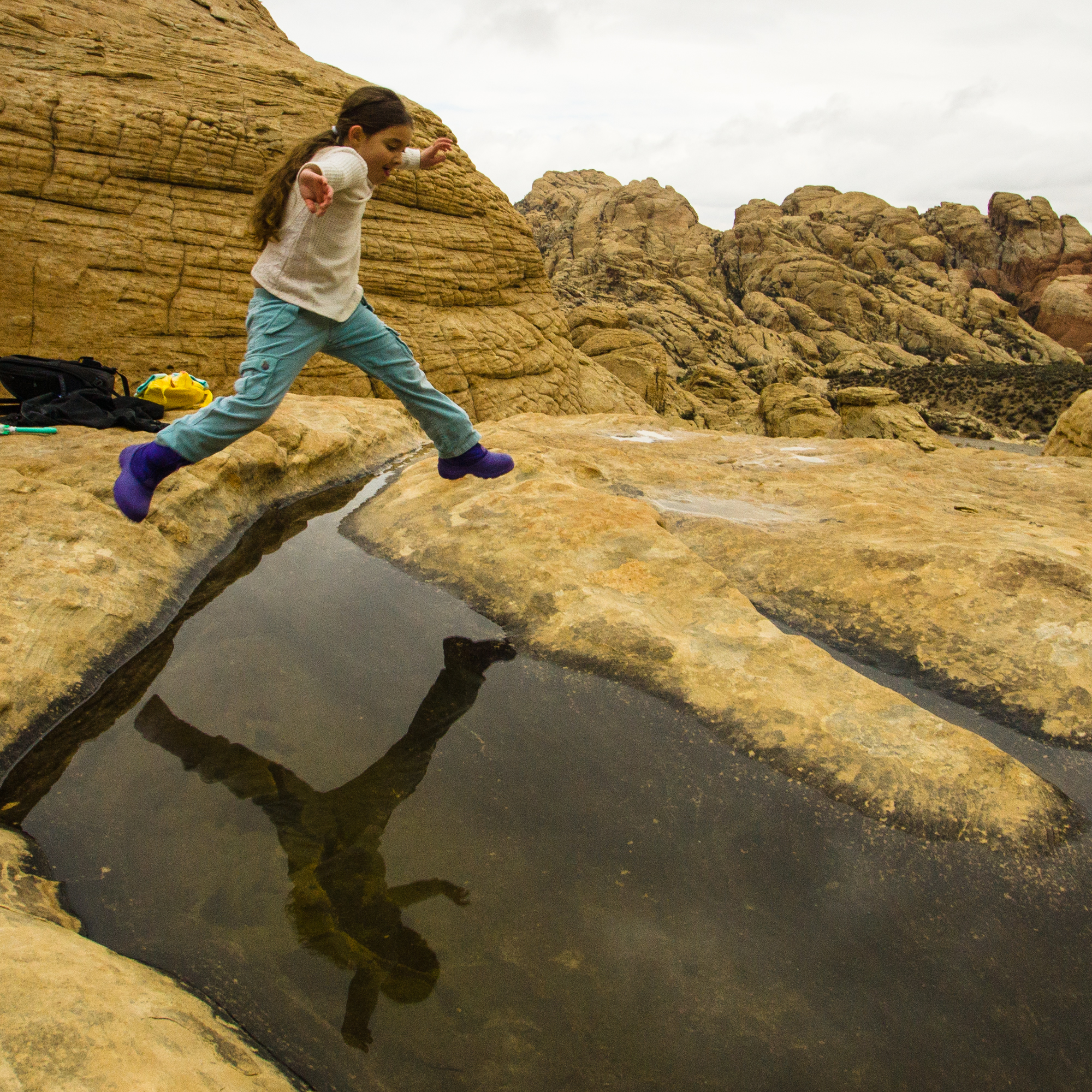 My Daughter reflected in a pool. If I was using a CPL then her reflection probably would be more defined and less of the rocks would be visible.