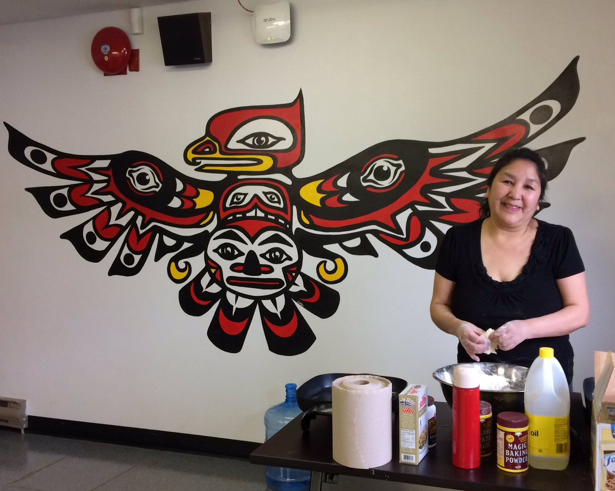 Mouat house mural in the background while a member of the community makes bannock for a program.