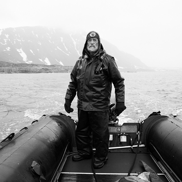"Here is an unpublished photo of Dr. Tom Smith, rifle master, naturalist, and what one of my friends calls ""the Chuck Norris of the Arctic"", scouting the land for polar bears ensuring that it's safe for us to land. I could tell stories all day about Tom, but my favorite story to tell is when he saved a polar bear's life by punching it in the face.     Join me this Thursday at 8 pm at Ira Lippke Studios in Chelsea, as I share more images and stories from my Arctic experience. I hope to see you there and share a glass of beer or wine with you!    #thisarcticlife #svalbard #arctic #polarbears #makeportraits #storyportrait"