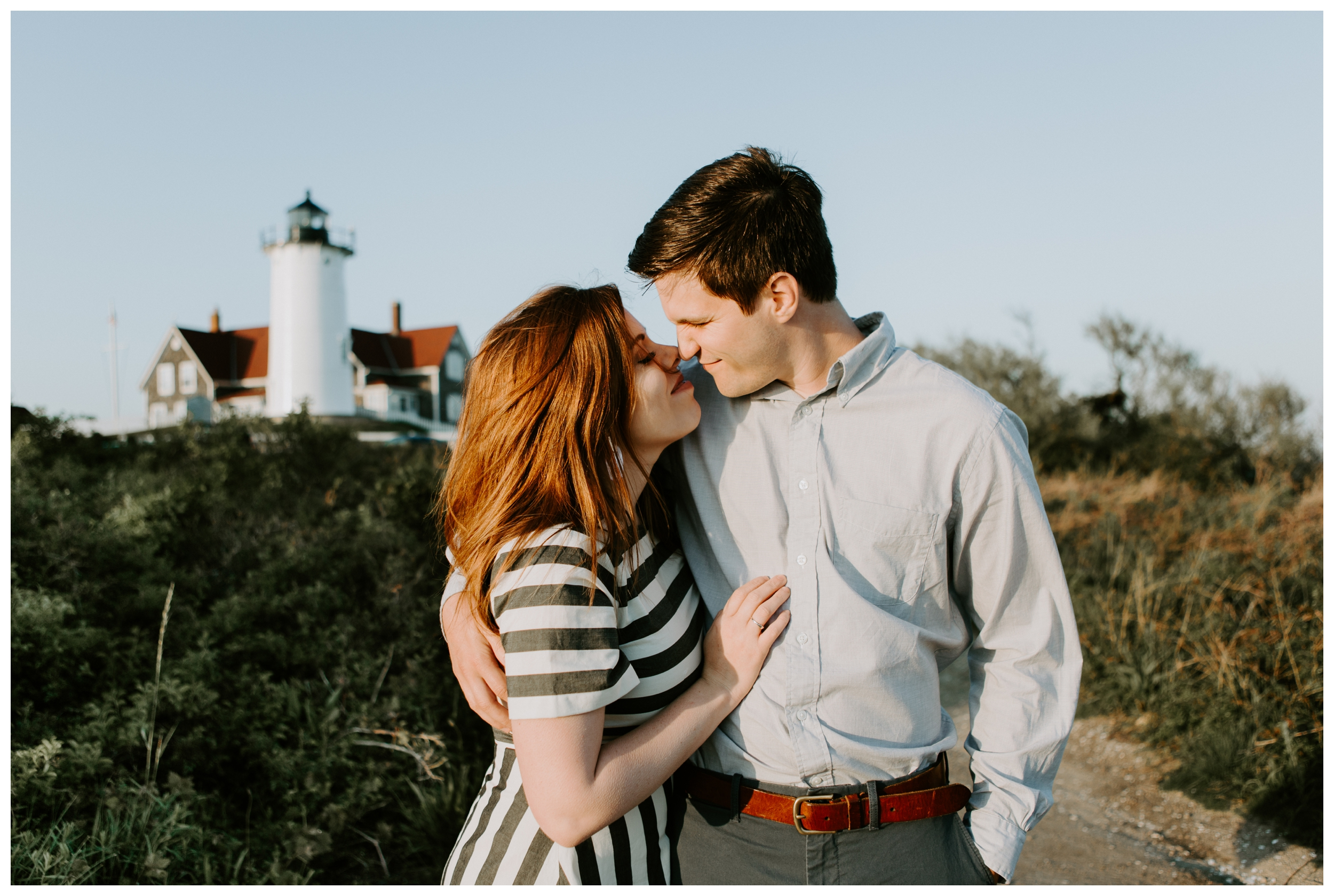 couple kisses in front of lighthouse