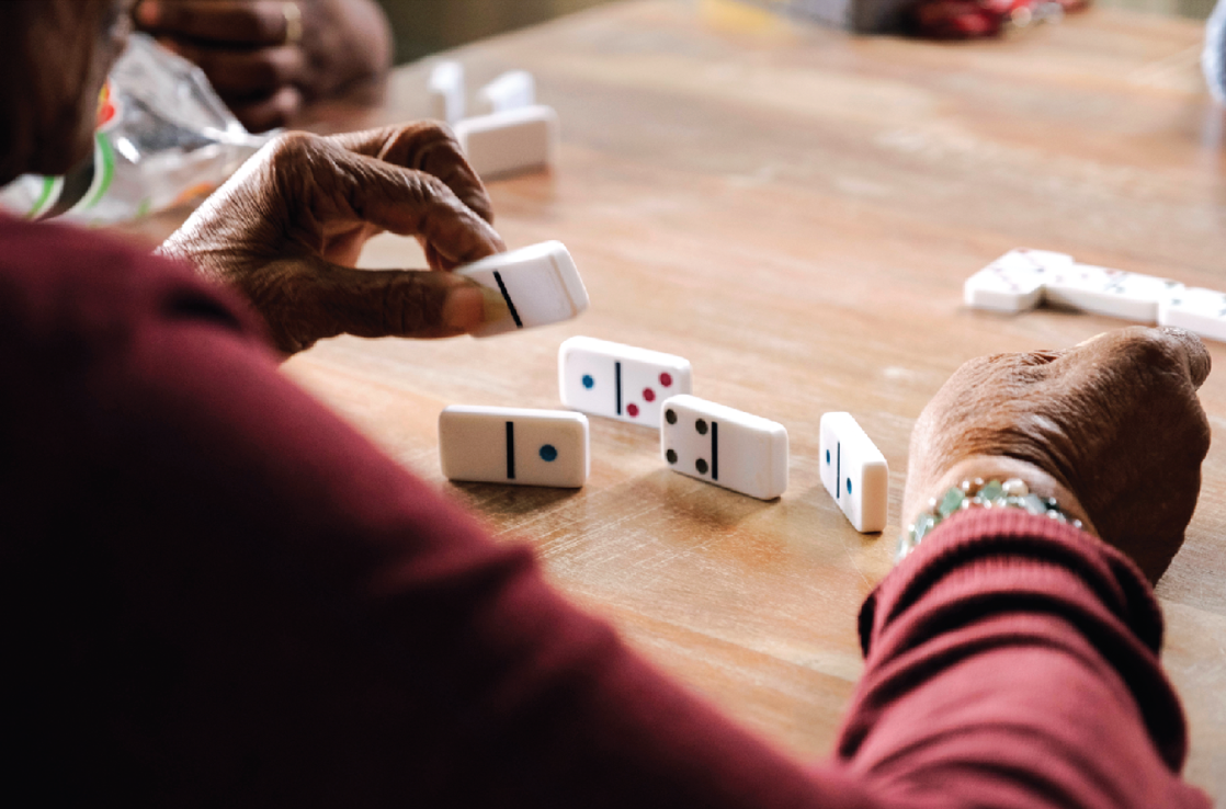 Participants playing dominoes at our Adult Day Program