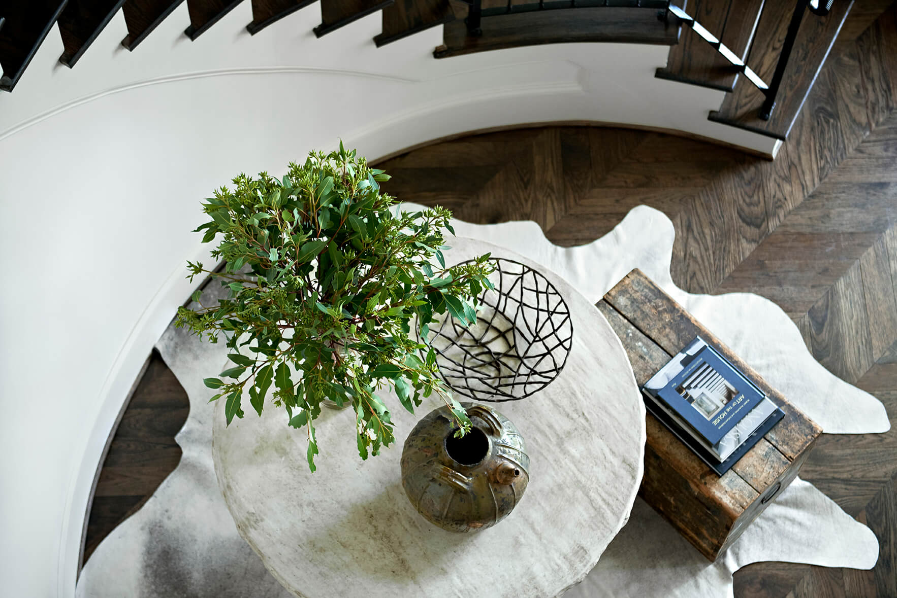 Bleached white round table next to an elegant staircase - Rustic Contemporary Bureau Interior Design Nashville TN