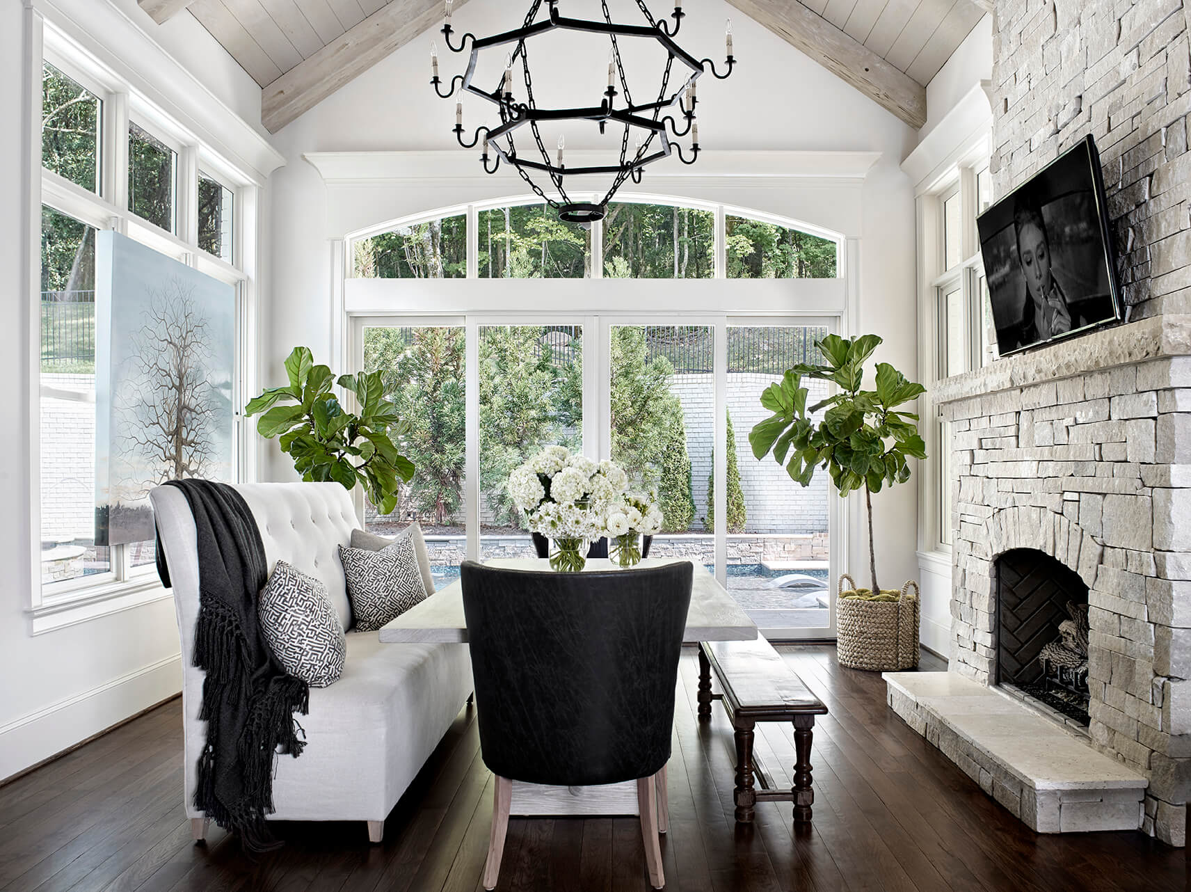 Dining area with stone fireplace and white and black furniture - Rustic Contemporary Bureau Interior Design Nashville TN
