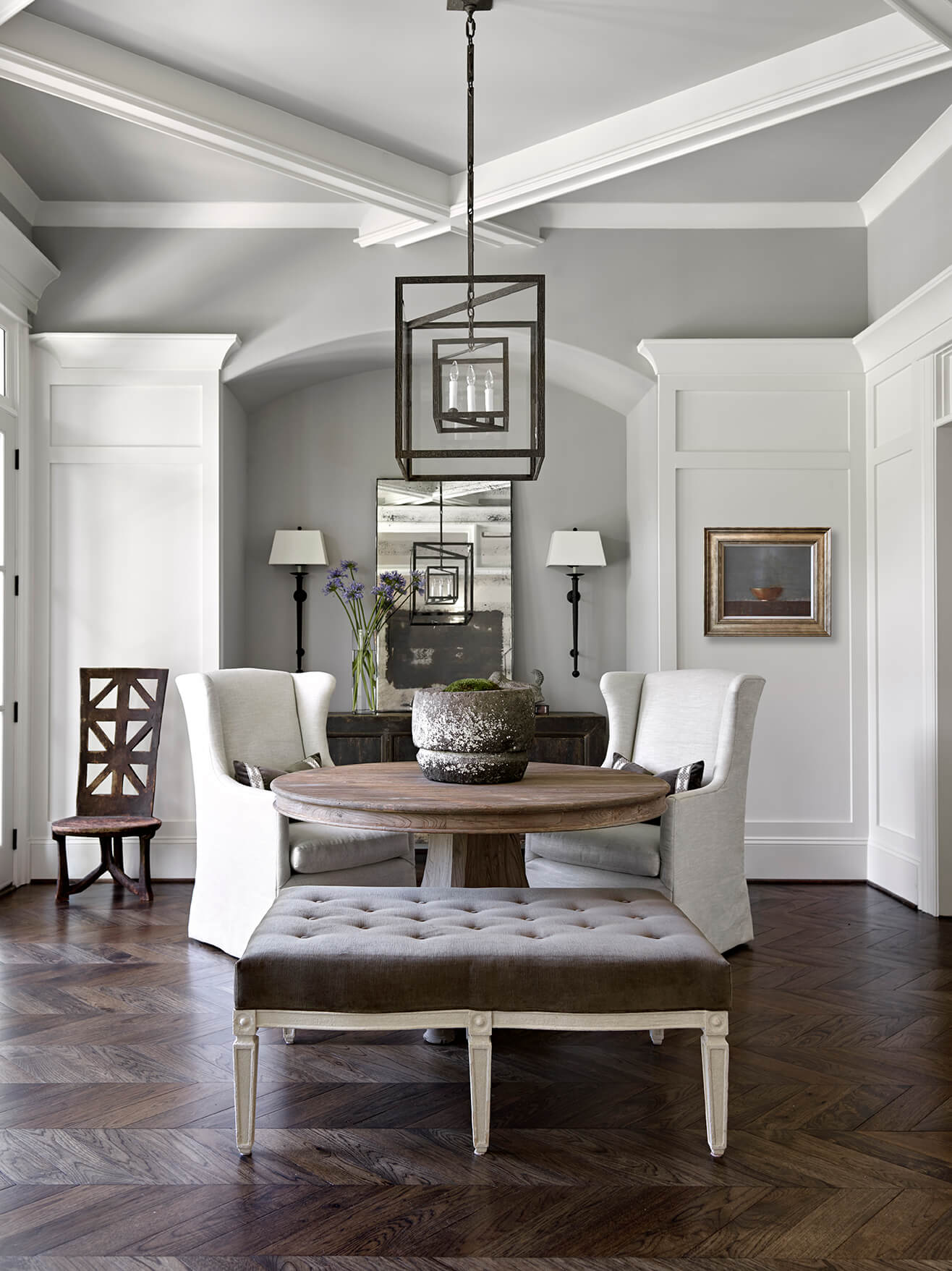 Small dining area with dark floors, gray upolstered bench and painted white walls - Rustic Contemporary Bureau Interior Design Nashville TN