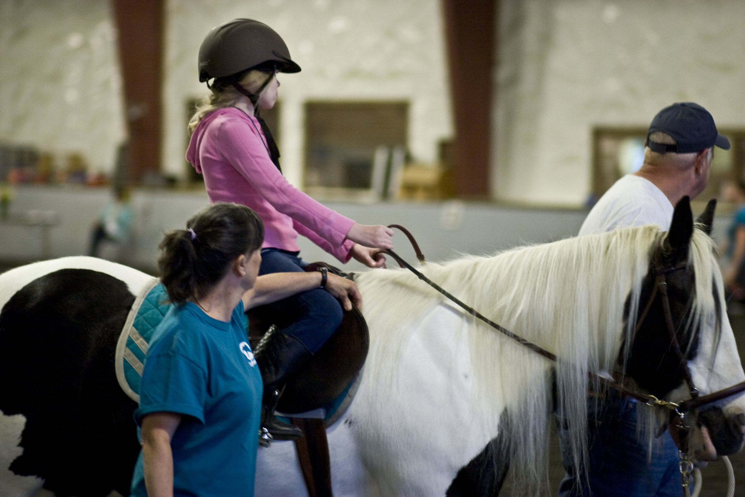 Side walker, Colleen, provides support to a  therapeutic riding  participant.