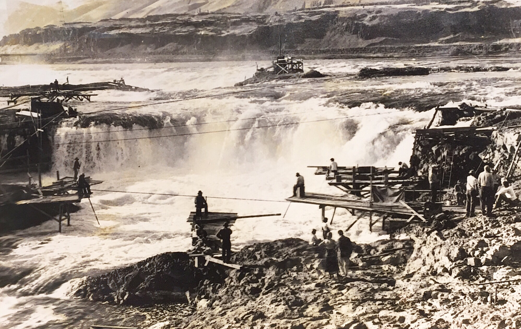 """This is a photo from the Washington State Historical archive that gives a great perspective on a Columbia River waterfall that was just a few miles down river from Maryhill Loops Road. This spot was called Wyam by First Nations peoples. Wyam meant """"echo of falling water"""" or """"sound of water upon the rocks"""". Later it became known as Celilo Falls. The area has known human habitation for 15,000 years. Until 1957, it was the oldest continually inhabited community on the North American continent. As the photo demonstrates, the reason for this was that it was an ideal, if not challenging, place to catch salmon. The tribes would build scaffolds out over the rapids from which to spear and net salmon as they moved up over the falls. There are some great videos on Youtube showing the falls and the people working them. The roar of the water was said to have been heard over a mile away.  It is hard to overstate how important these falls were to the native peoples who gathered and lived here. Not only as a food source but also as a melting pot for the different cultures that came. The river, as wide as one mile in places, choked down to just 140 feet wide at the falls. In the twelve subsequent miles below Celilo, the river dropped 82 feet. This section of narrows was referred to as the Dalles. Celilo Falls was sixth largest in the world by volume. It is estimated that 15 to 20 million salmon passed over the falls every year. The area also served as a crossroads between two major cultures. From the Northwest came people who spoke Chinookian languages and from further east came those who spoke Sahaptian languages. Both pulling in trade goods from as far afield as the Great Plains, Alaska and the American Southwest. Near the falls, there were two major villages. On the north bank lived the Wishram people and the south bank was populated by the Wasco. The most intense trading apparently occurred at Nix-Luidix, the Wishram village on the north bank. It has been called the Wall Street """
