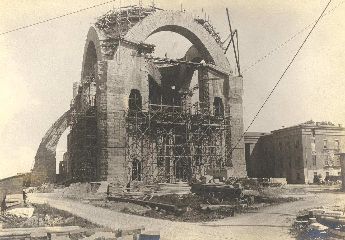 1909: The central crossing photographed from where the nave now stands. Heins & LaFarge's insistence on stone construction led them to erect gigantic catenary arches, supported at the corners by buttresses, as the base of what was to be a tower and dome more than 100 meters tall. Embracing half measures to open by 1911, the cathedral erected temporary walls on all three sides and had Guastivino build a temporary dome on top. Credit: Episcopal Diocese of New York Archives