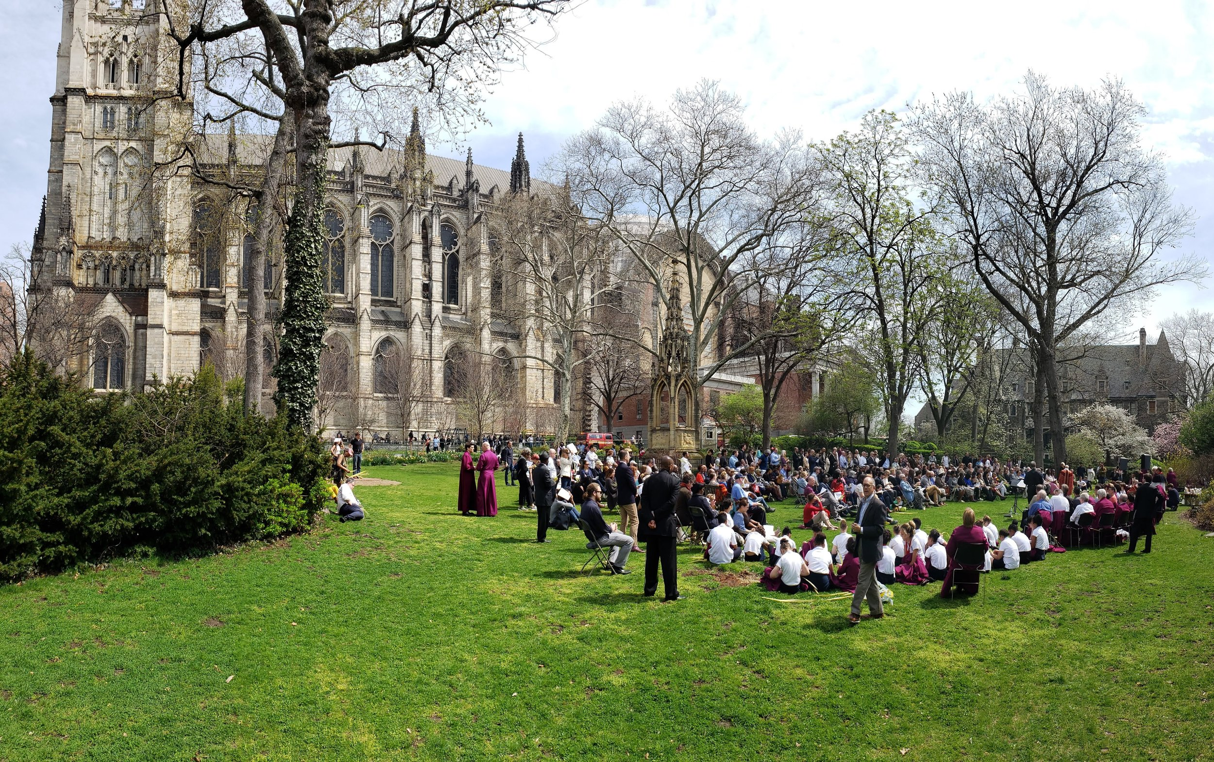 2019, April 14: On Palm Sunday this year, a small fire broke out in the basement less than an hour before the service began. As emergency workers controlled it, the clergy and congregation decamped to the adjacent yard and held mass. For an hour, St. John the Divine was an institution without a cathedral. Credit: Photo by the author